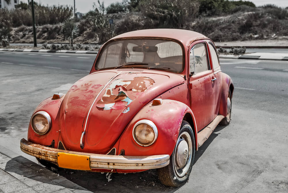 old looking car with oxidation and peeled off paint