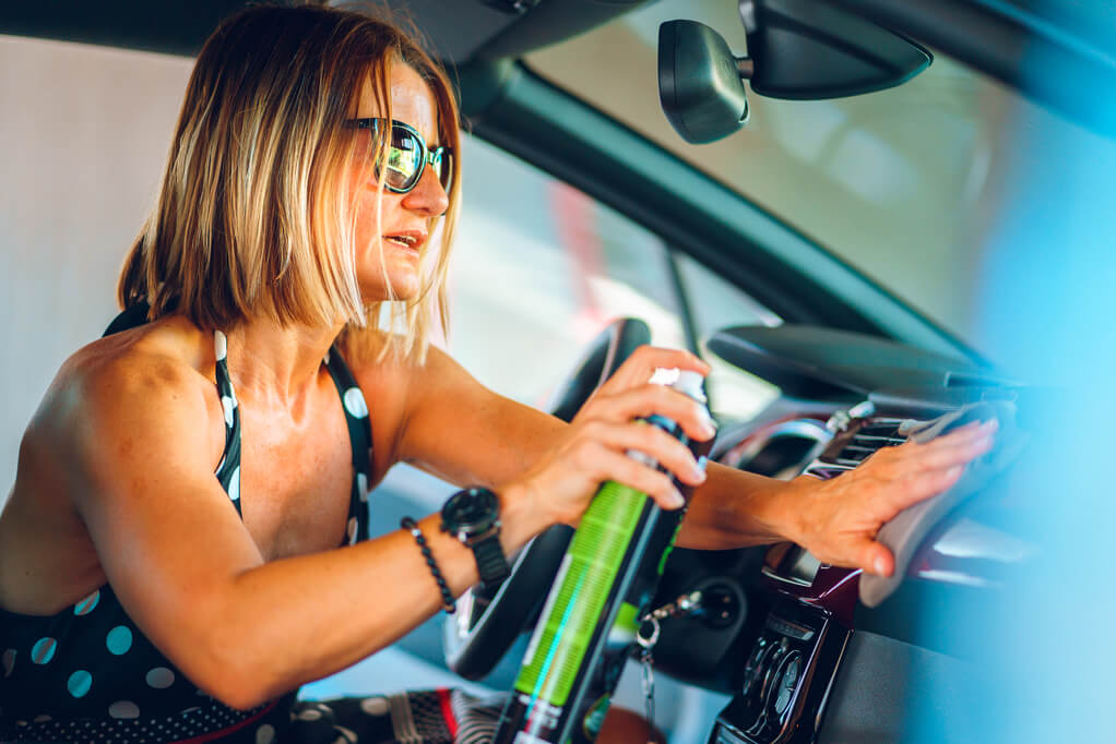 woman detailing car's interior